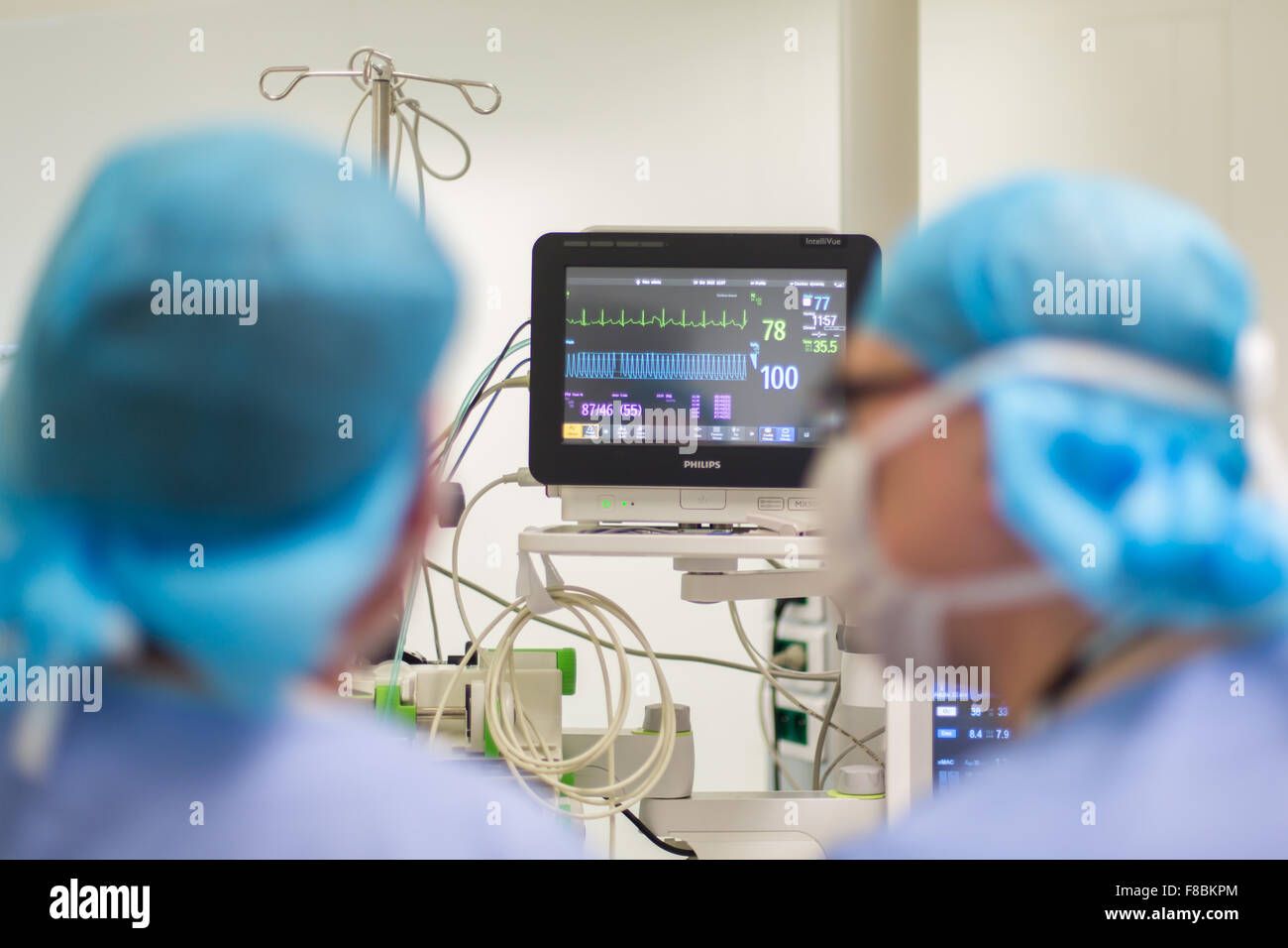 Surgical monitors being used to track the vital signs of a patient during an operation. - Stock Image