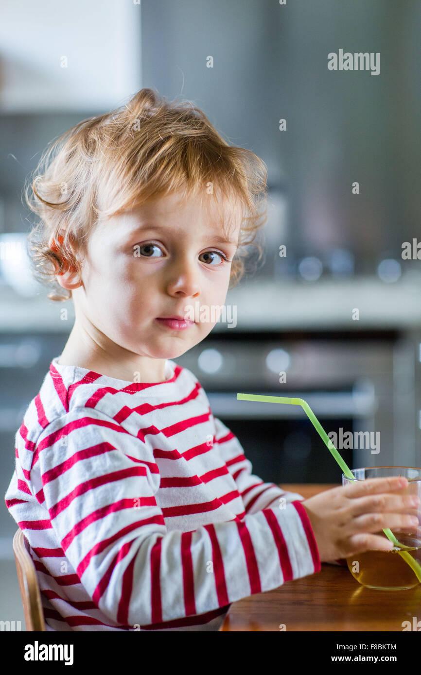 2 year-old boy drinking fruit juice. - Stock Image