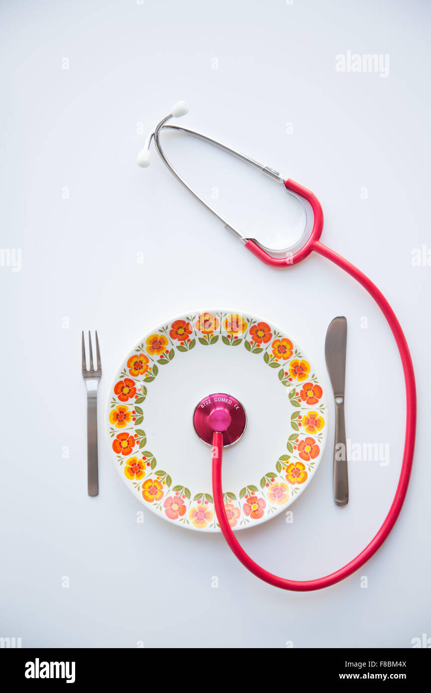 Stethoscope on a plate. Conceptual image about the benefits of a balanced diet on health. - Stock Image