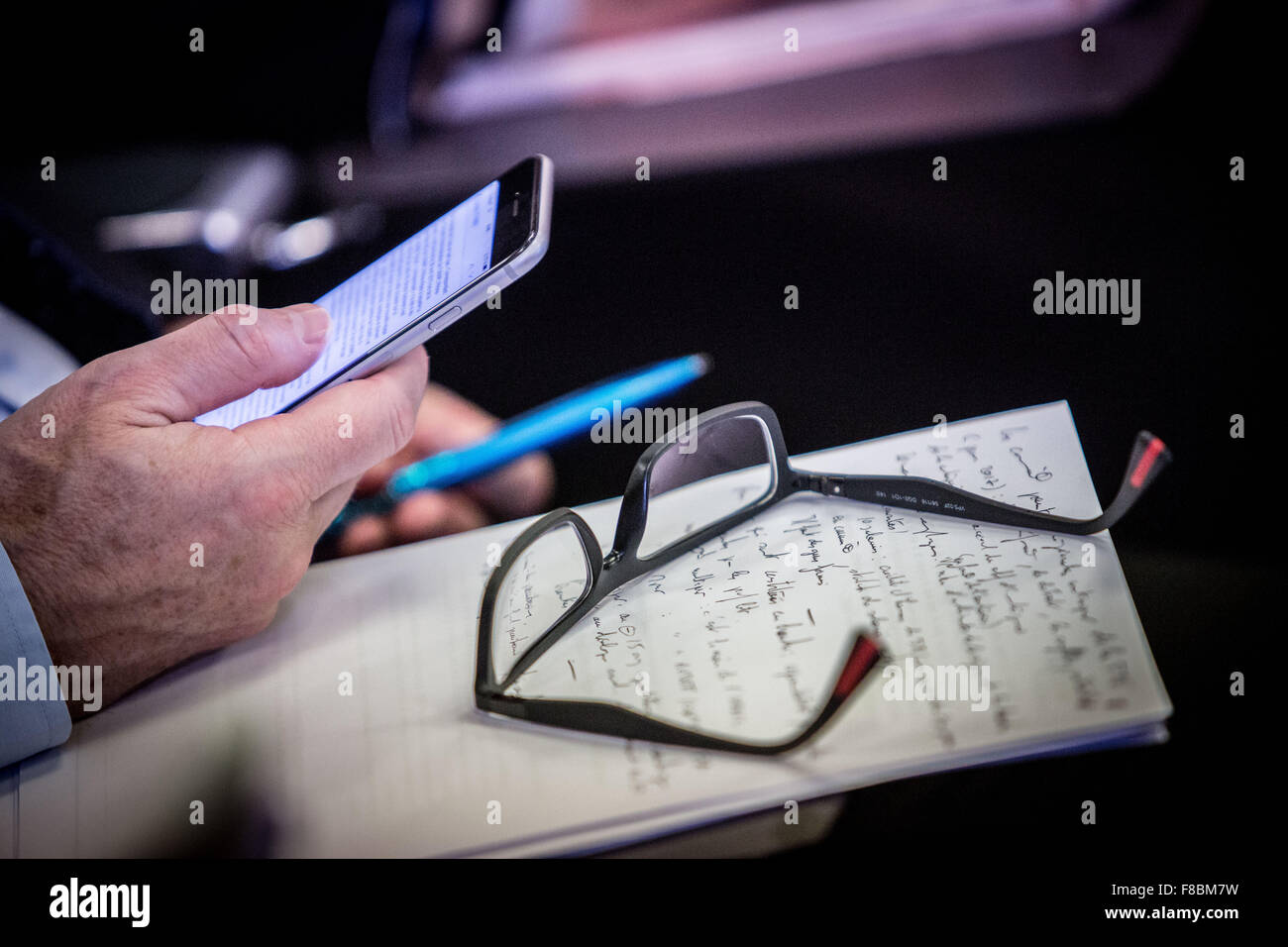 Man using his cell phone during a meeting. - Stock Image