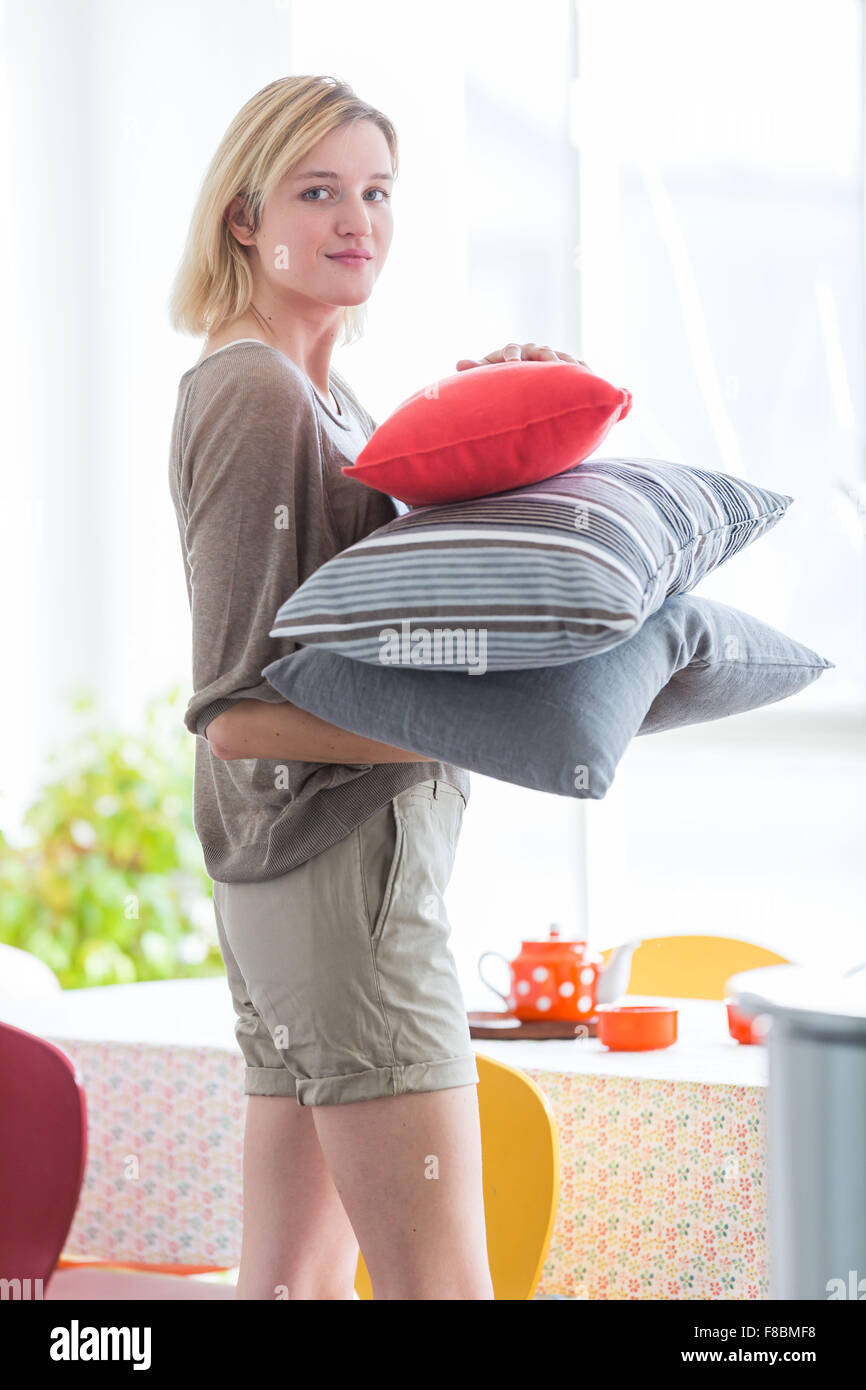 Woman holding pillows. - Stock Image
