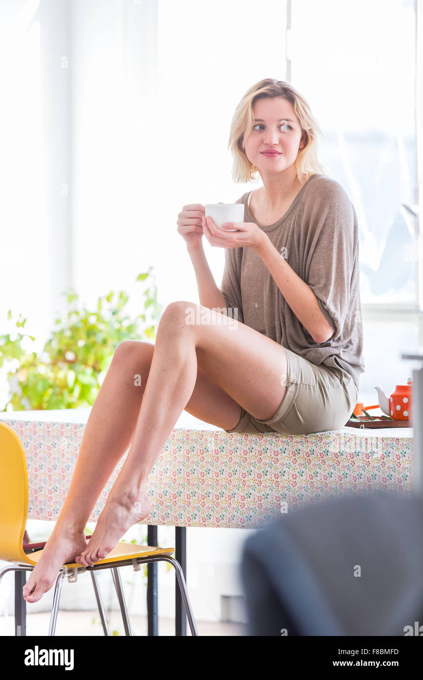 Woman drinking hot beverage. - Stock Image