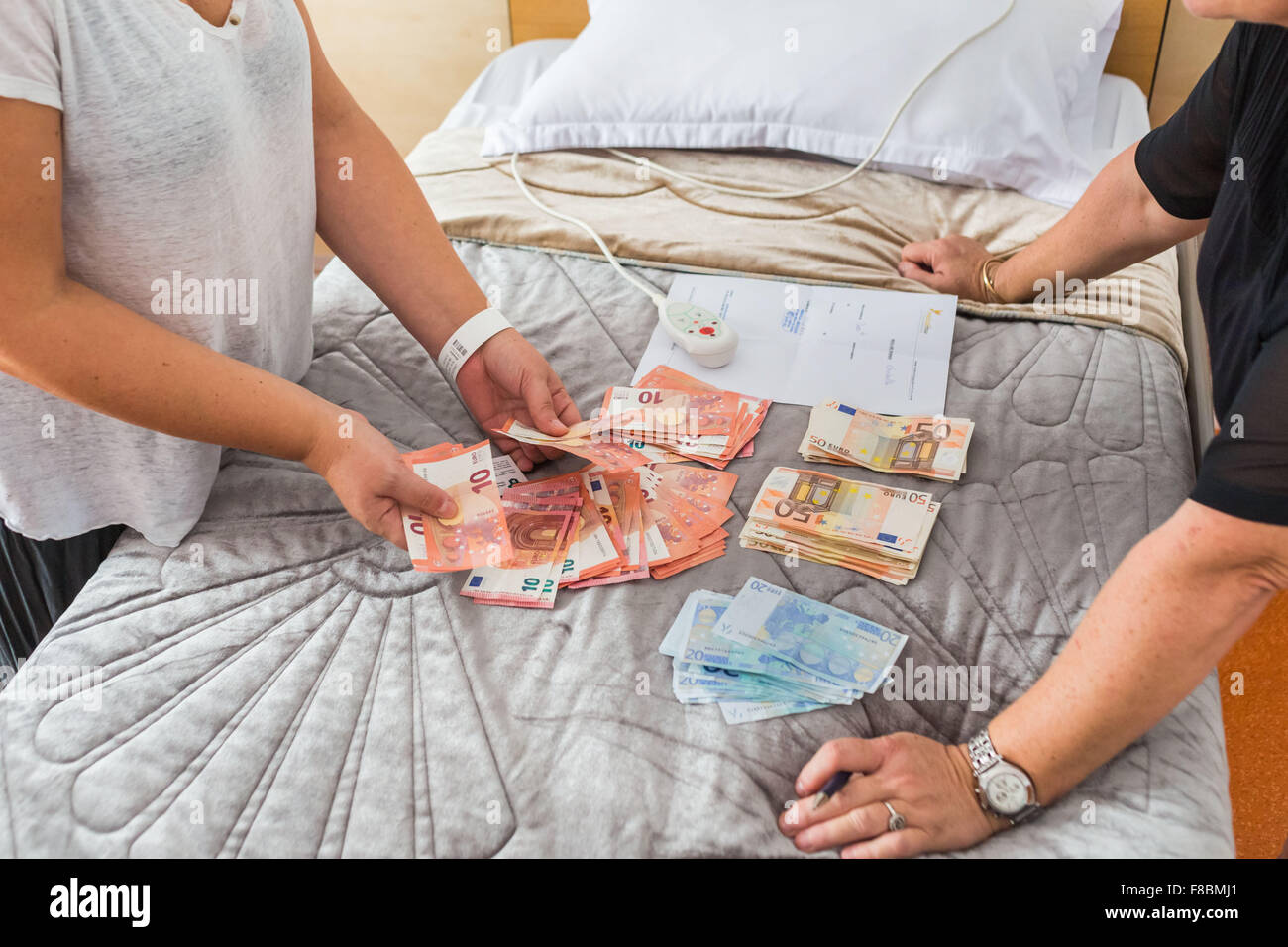 Woman paying in cash a cosmetic surgery abroad. - Stock Image