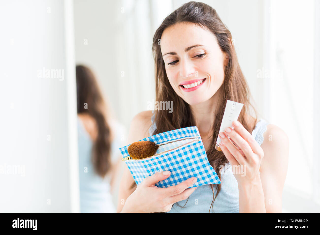 Woman reading the composition of cosmetic product. - Stock Image