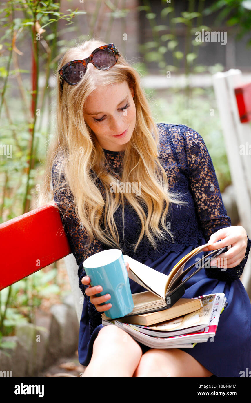 Portrait of attractive female student reading book, while sitting at campus area. Student life. - Stock Image