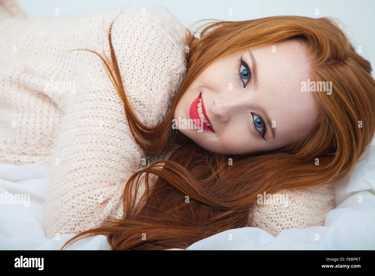 A pretty redheaded woman lying down on white fabric. - Stock Image