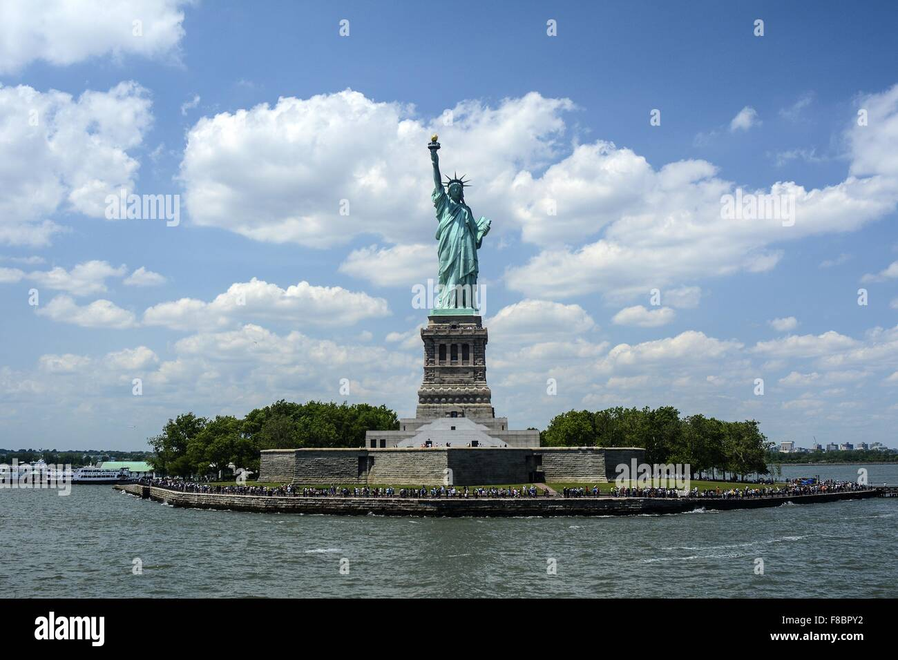 Statue of Liberty in the distance with blue sky and clouds Stock Photo