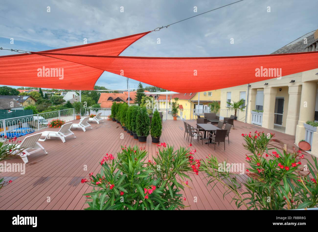 Terrace in summer with shade sails, flowers and deck chairs Stock Photo