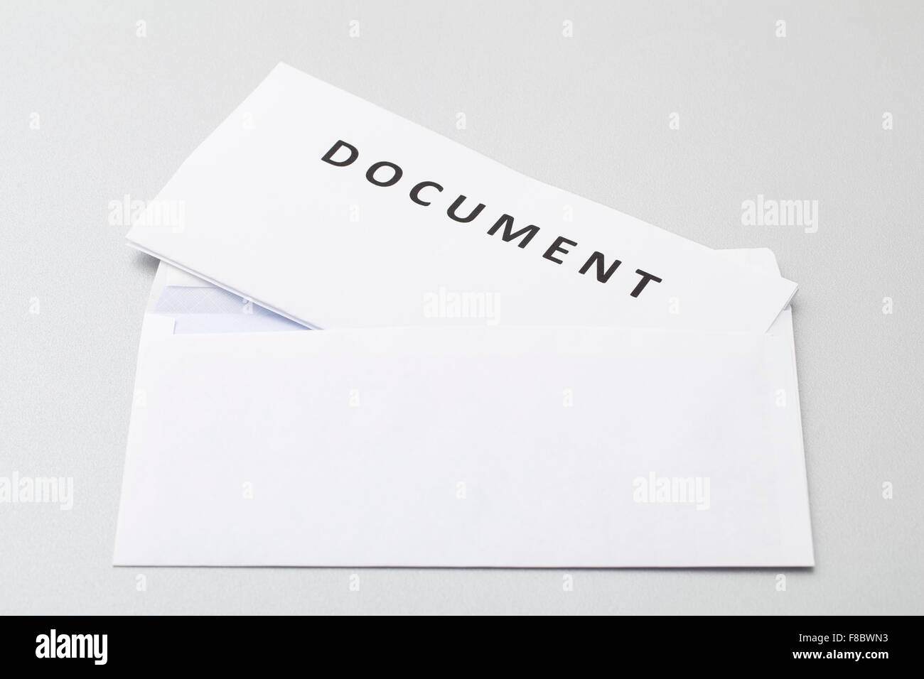 Folded white sheets document put in blank white envelope, isolated on background. - Stock Image