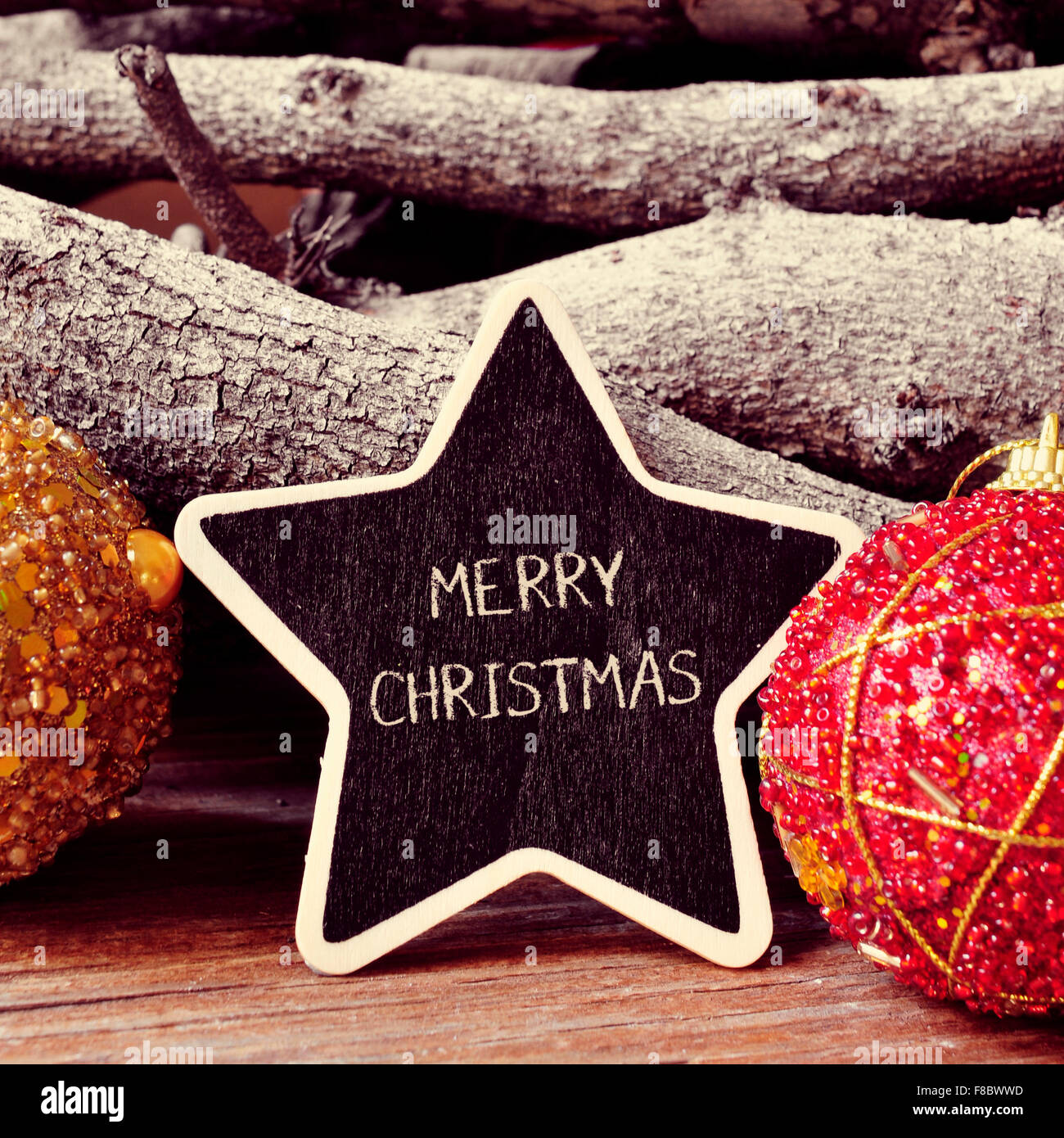 the text merry christmas written in a star-shaped blackboard, and some christmas ornaments, and pinecones and a - Stock Image