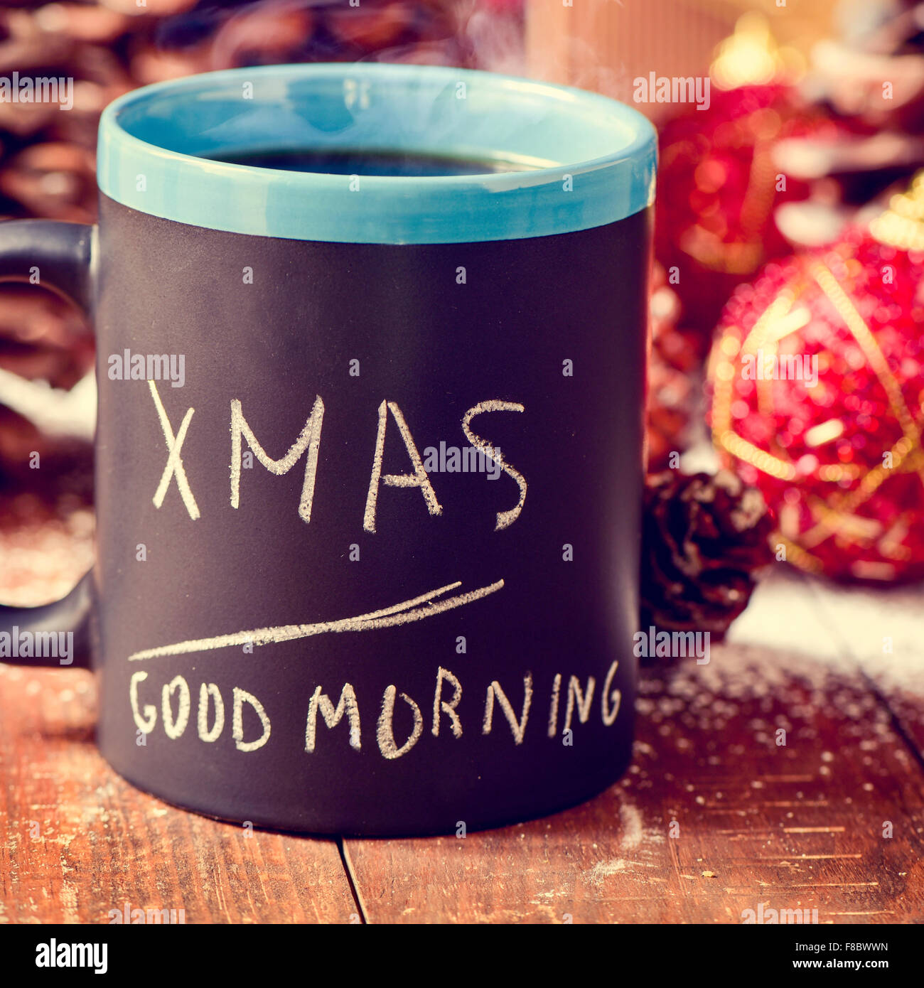 text xmas good morning written in a black mug with coffee or tea on a rustic wooden table with some pinecones and - Stock Image