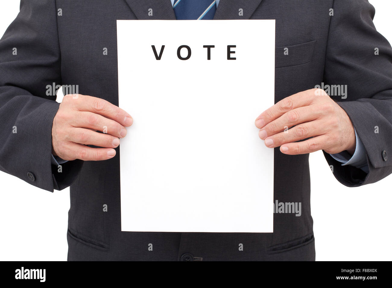 Man in suit, holding a white sheet with title VOTE in front of him. The image has been made in studio and isolated - Stock Image
