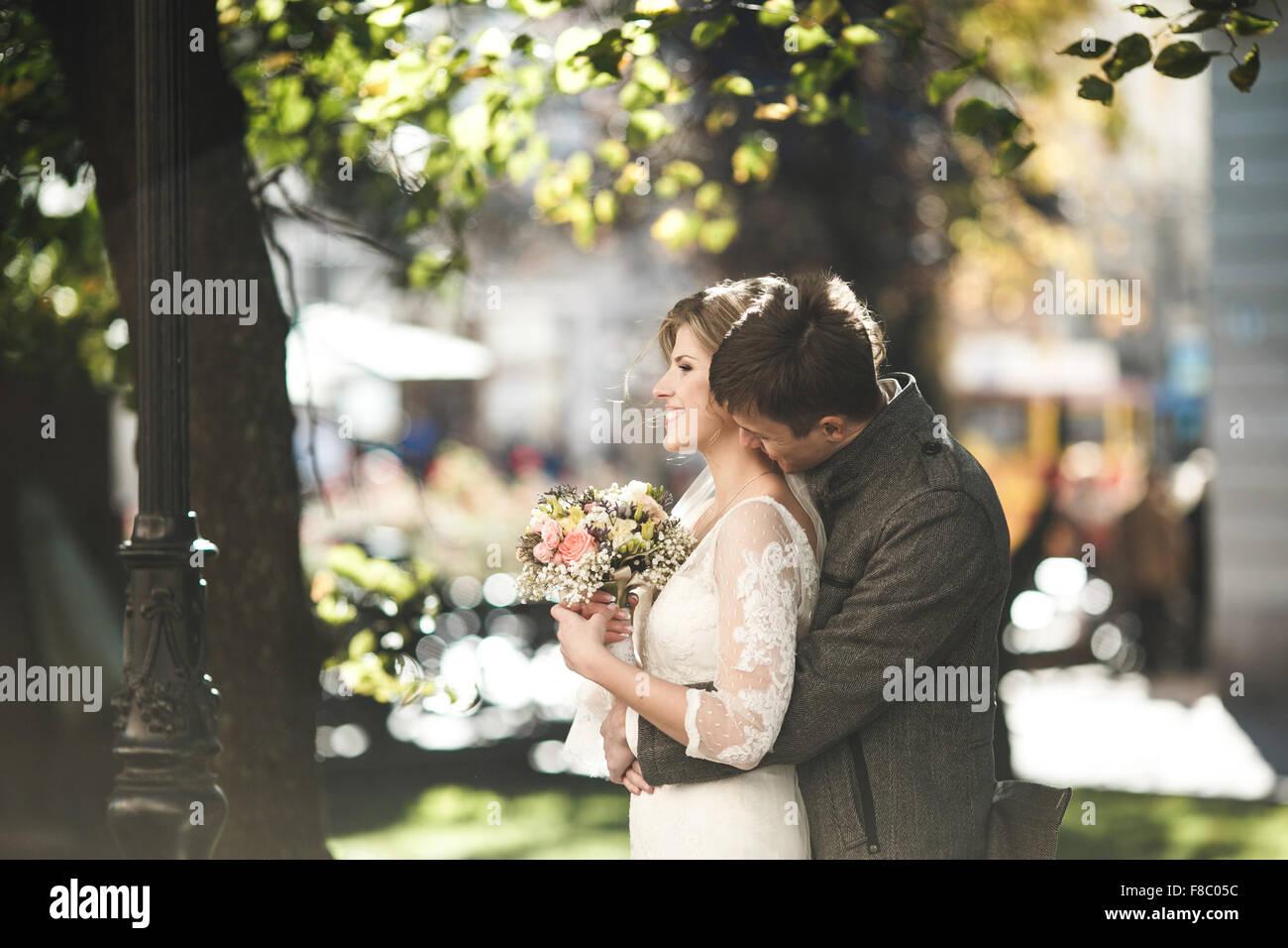 Groom hugs bride - Stock Image