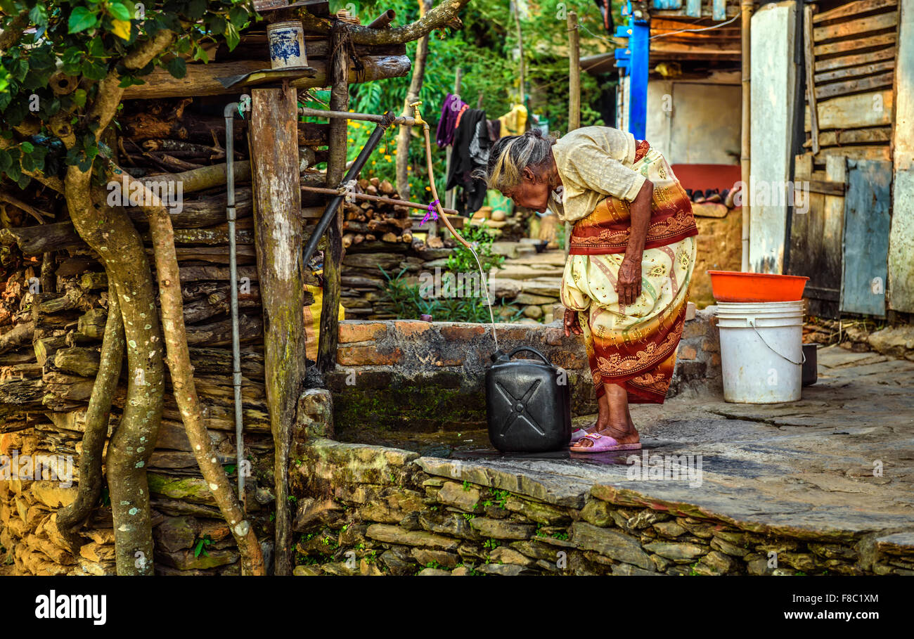 Very old hunched woman fills a jerrycan with water - Stock Image
