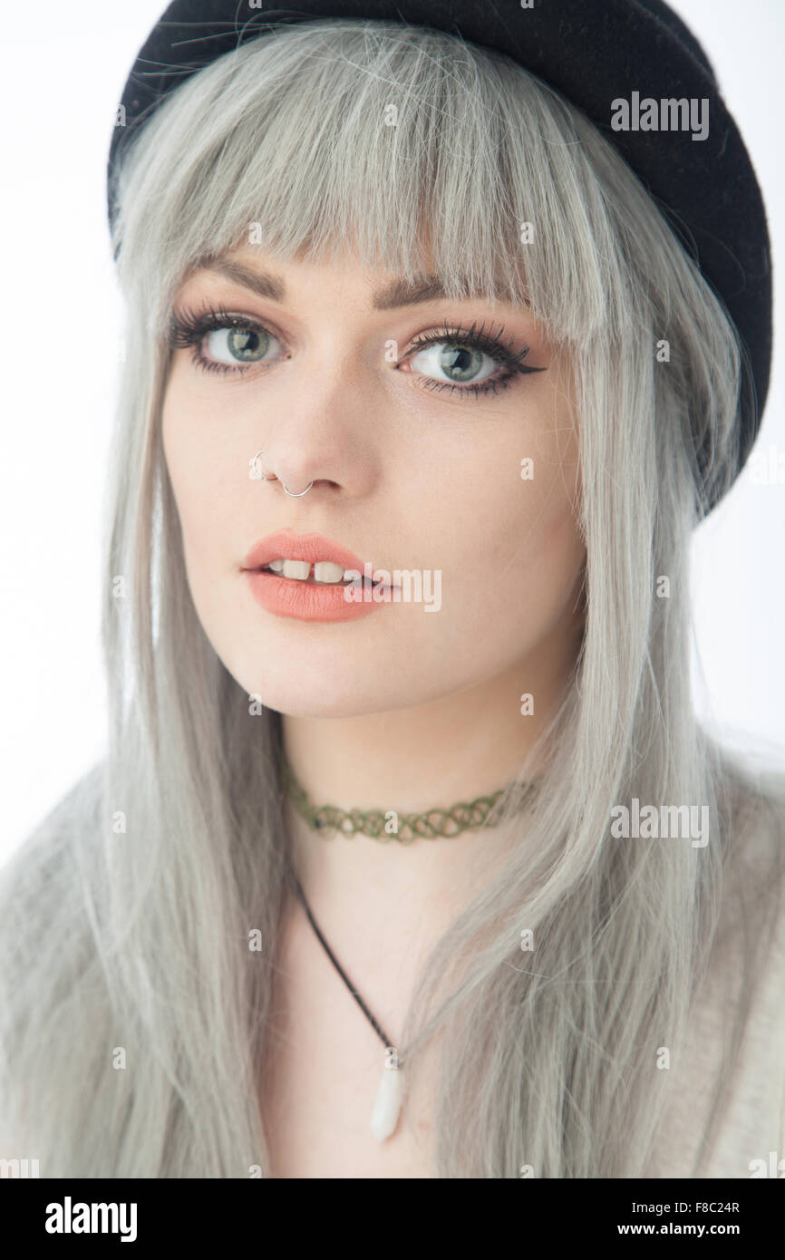Portrait of an eighteen year old woman with dyed gray hair and a gap between her front teeth. - Stock Image