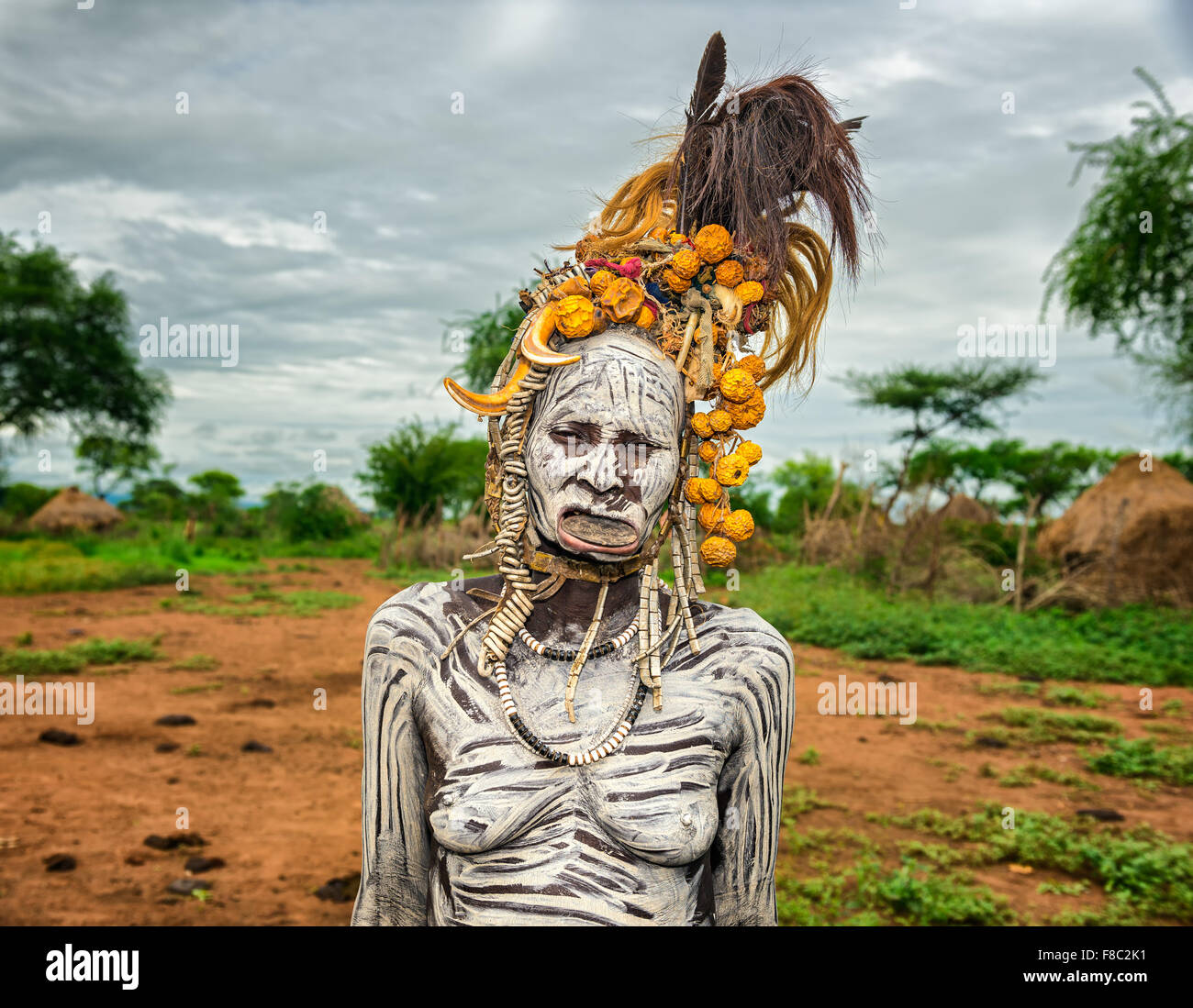 Old woman from the african tribe Mursi with lip plate in her village - Stock Image