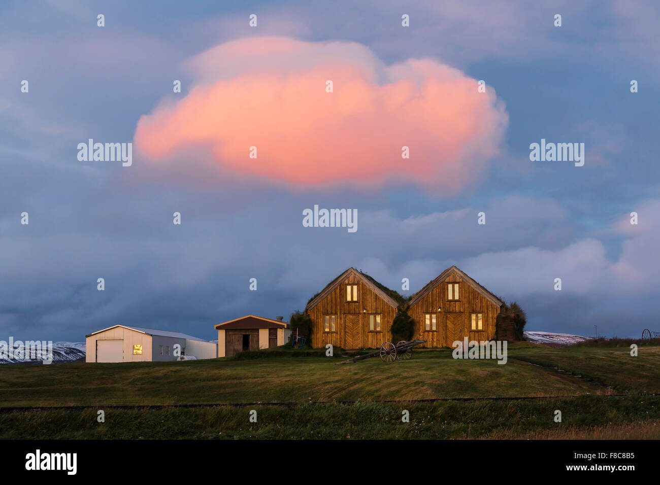 Turf covered houses at Modrudalur. Gorgeous red cloud over houses. North Iceland - Stock Image