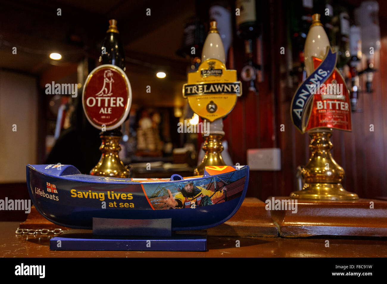 Saving Lives at Sea, the ubiquitous RNLI charity lifeboat moneybox found in seaside pubs. - Stock Image