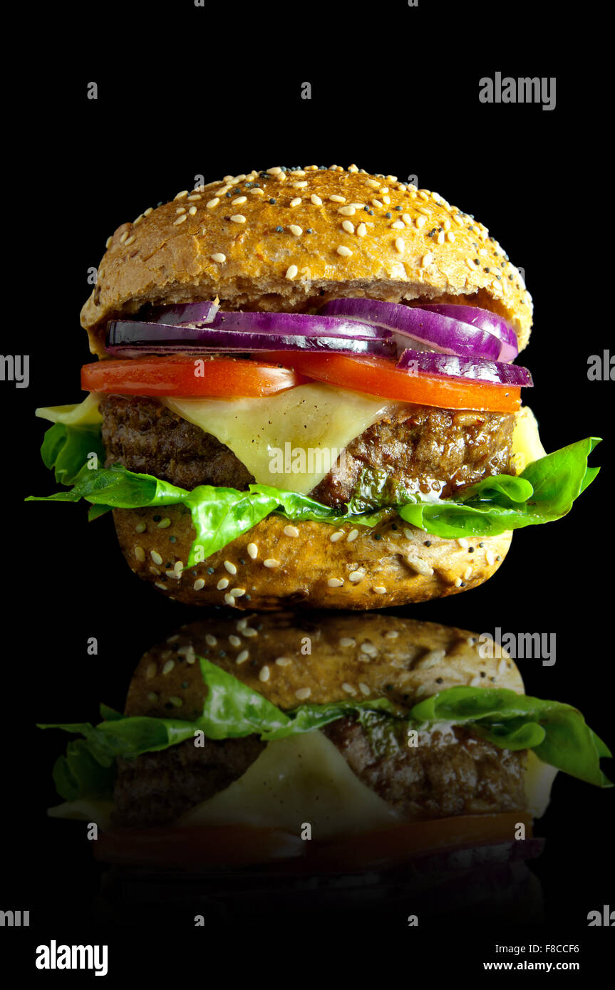 Freshly made burger with melted cheese, onions, tomatoes and lettuce filling - Stock Image