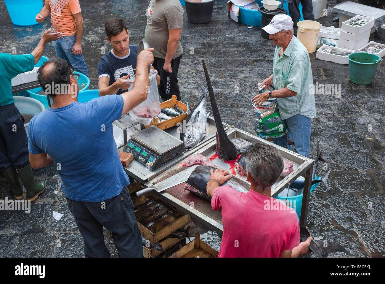 Catania fish market, view of a man buying swordfish on a busy morning in Catania's famous fish market (Mercato - Stock Image