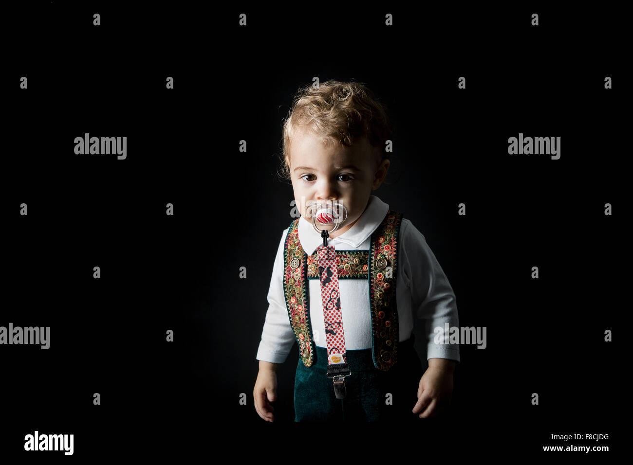 an 18 month young boy wearing lederhosen sucks on a pacifier - Stock Image