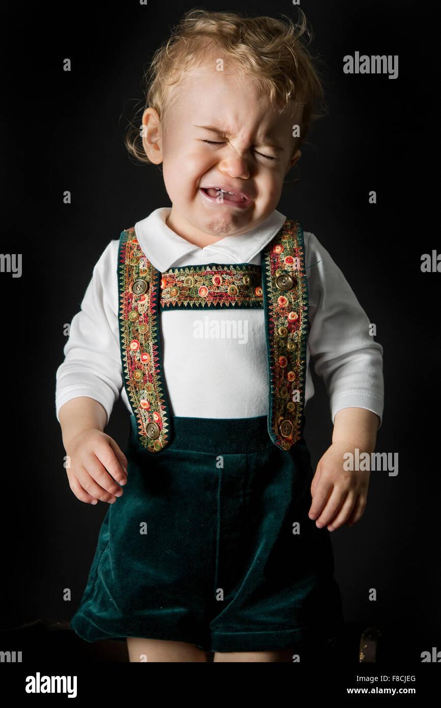 An 18 month old boy wearing lederhosen cries - Stock Image