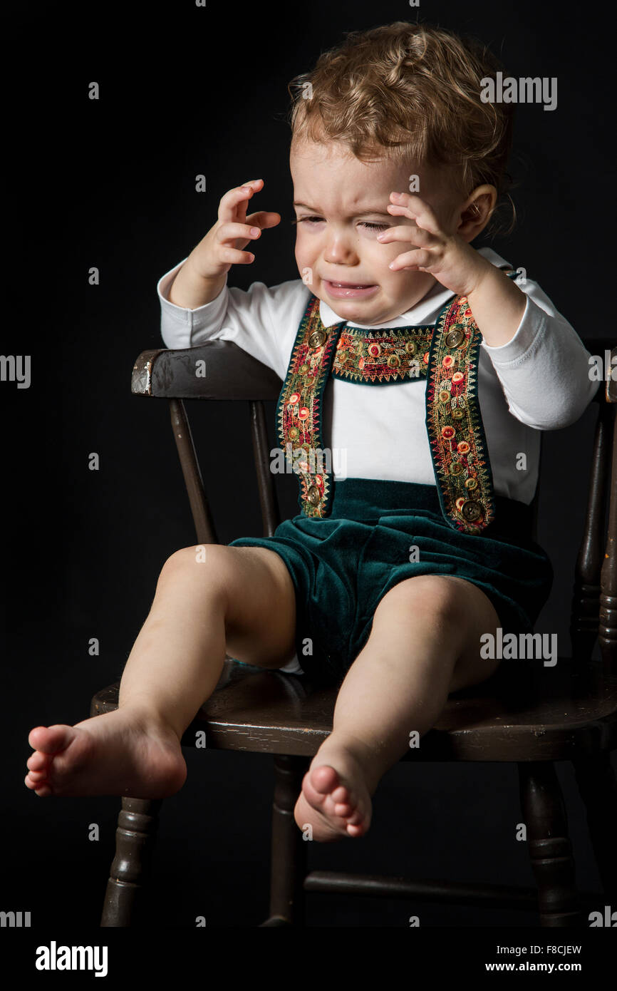 An 18 month old boy wearing lederhosen cries while he's sitting on a wooden chair. - Stock Image