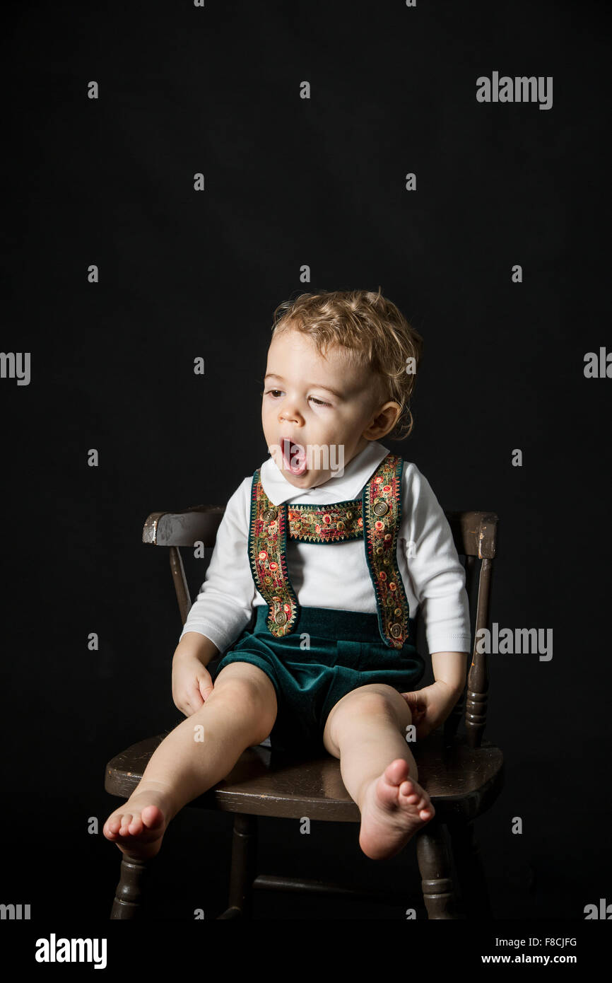An 18 month old boy wearing lederhosen yawns while he's sitting on a wooden chair. - Stock Image