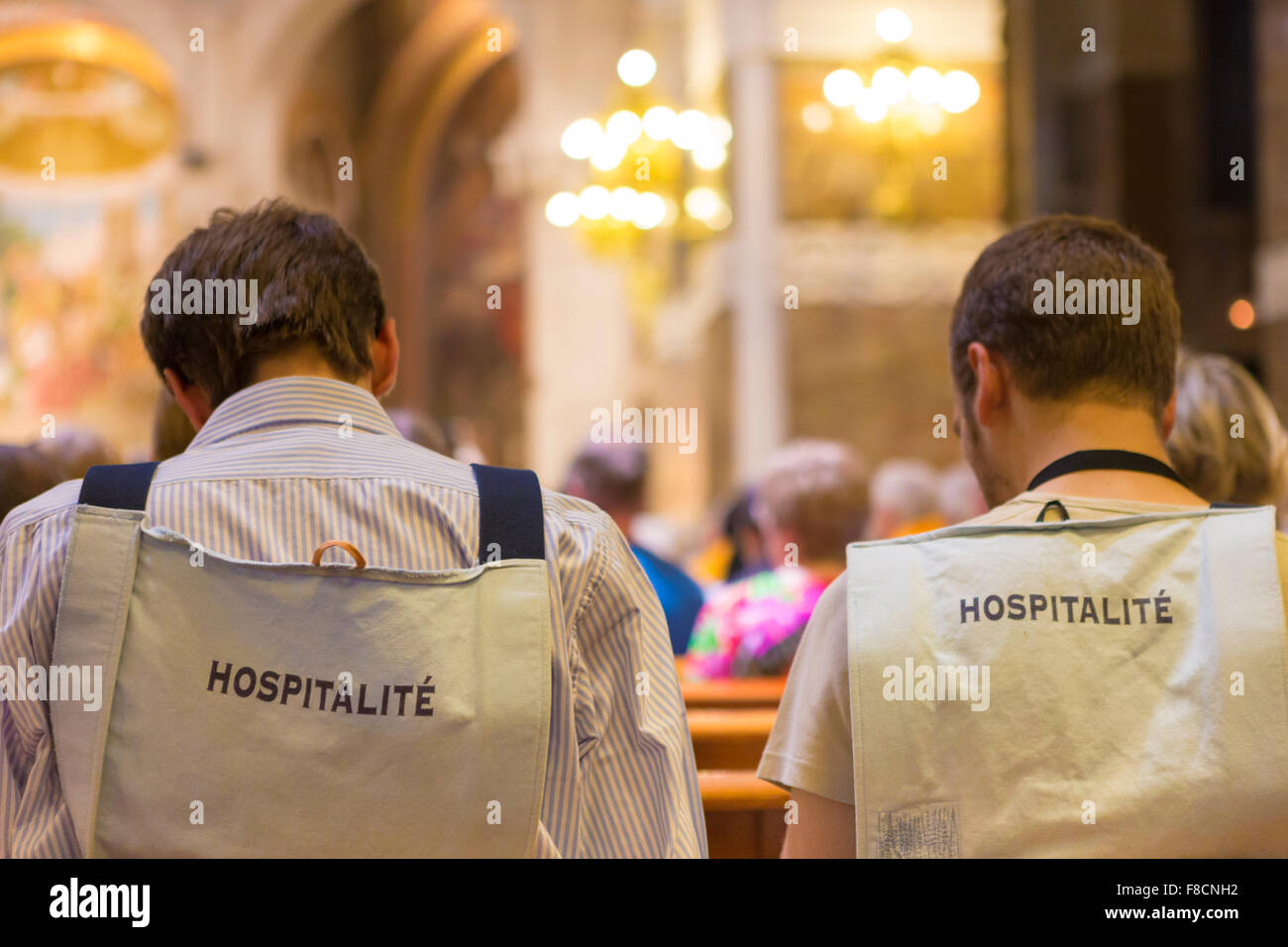 Back of volunteers in Lourdes in the church of Lourdes - Stock Image