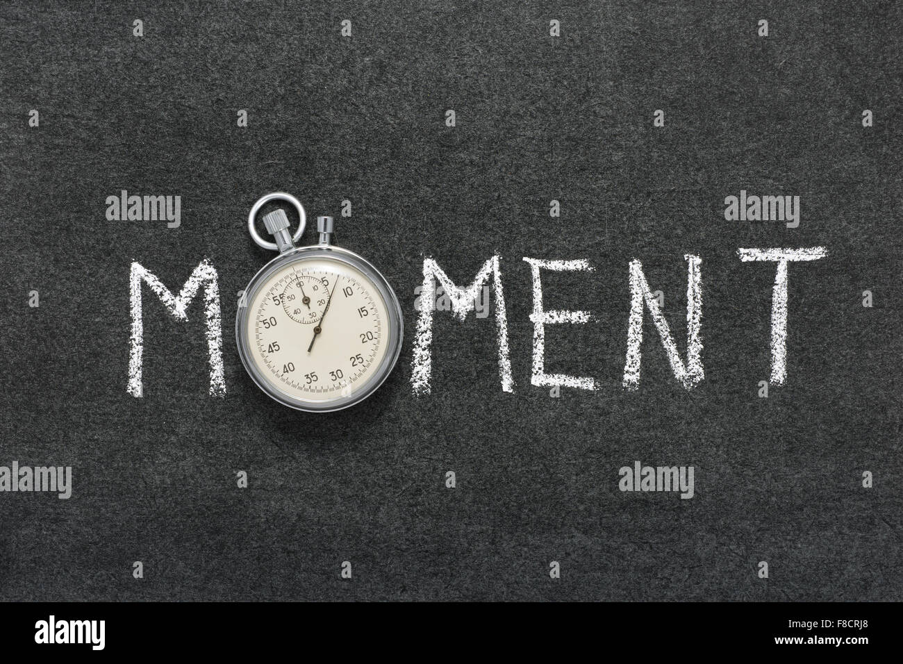 moment word handwritten on chalkboard with vintage precise stopwatch used instead of O - Stock Image