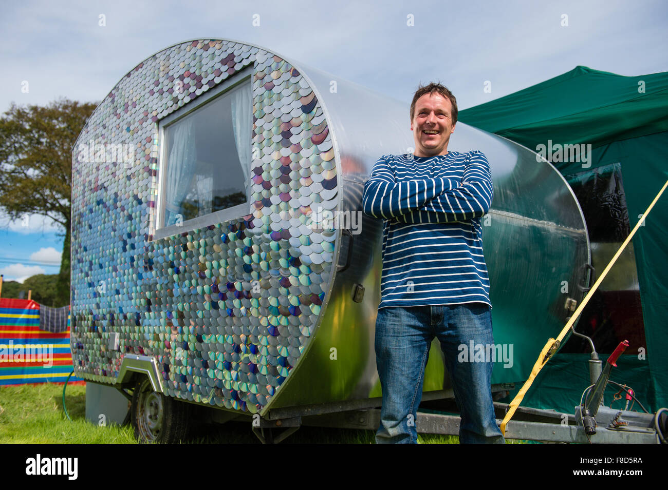Craftsman and maker Carwyn Lloyd Jones, standing outside  his small wooden-framed caravan which he made himself - Stock Image