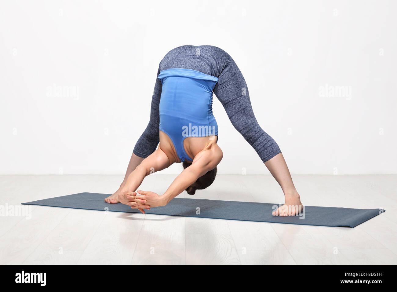Woman practices Ashtanga Vinyasa yoga asana - Stock Image