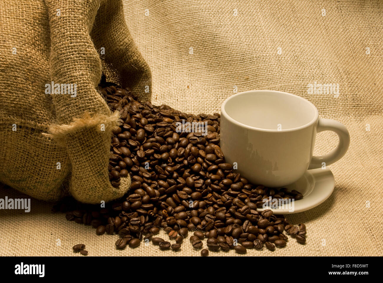 Cup and Saucer With Coffee Beans Pouring From Burlap Bag on a Burlap Background - Stock Image