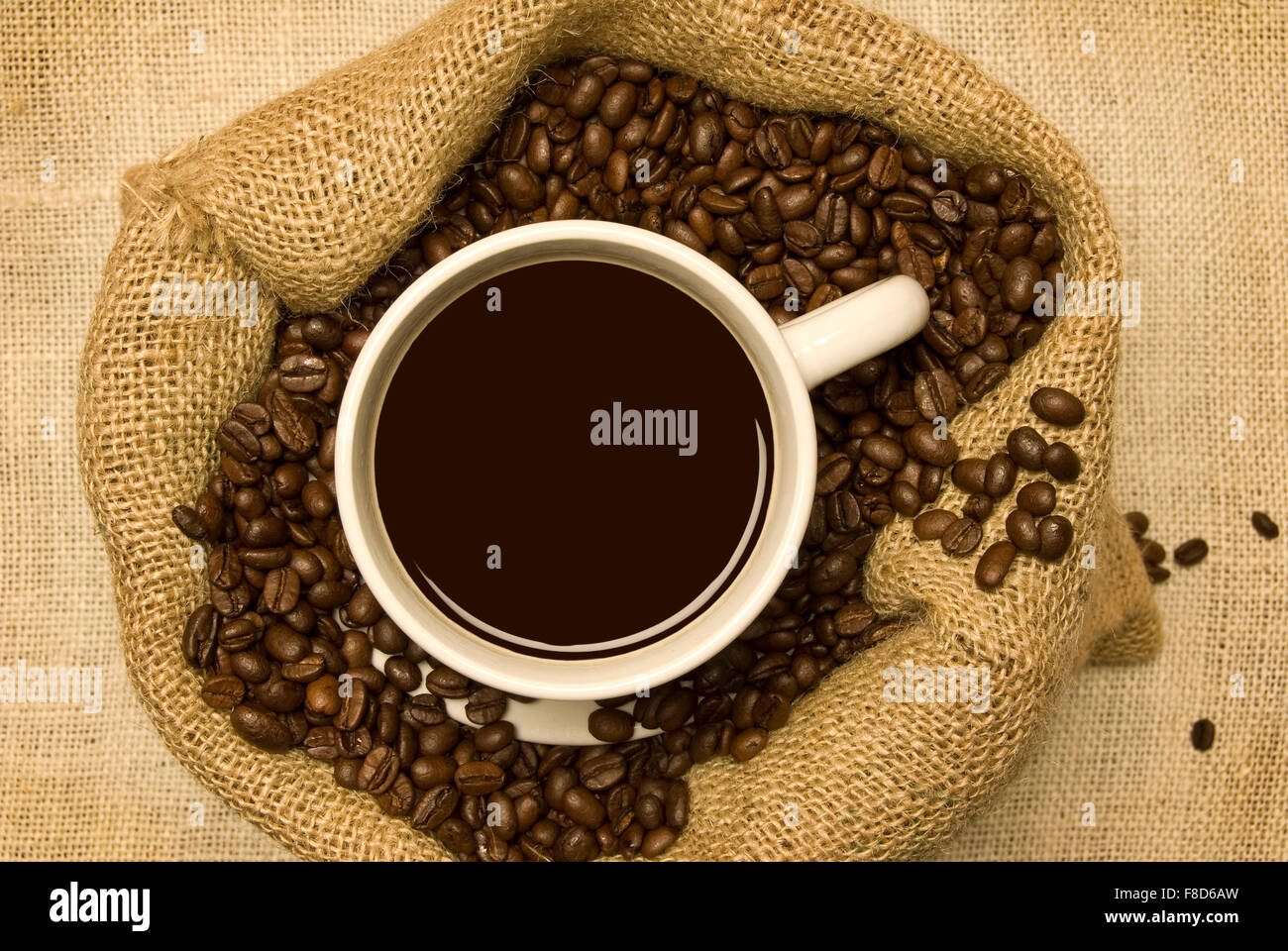 Cup of Coffee Sitting in Coffee Beans in Burlap Bag - Stock Image