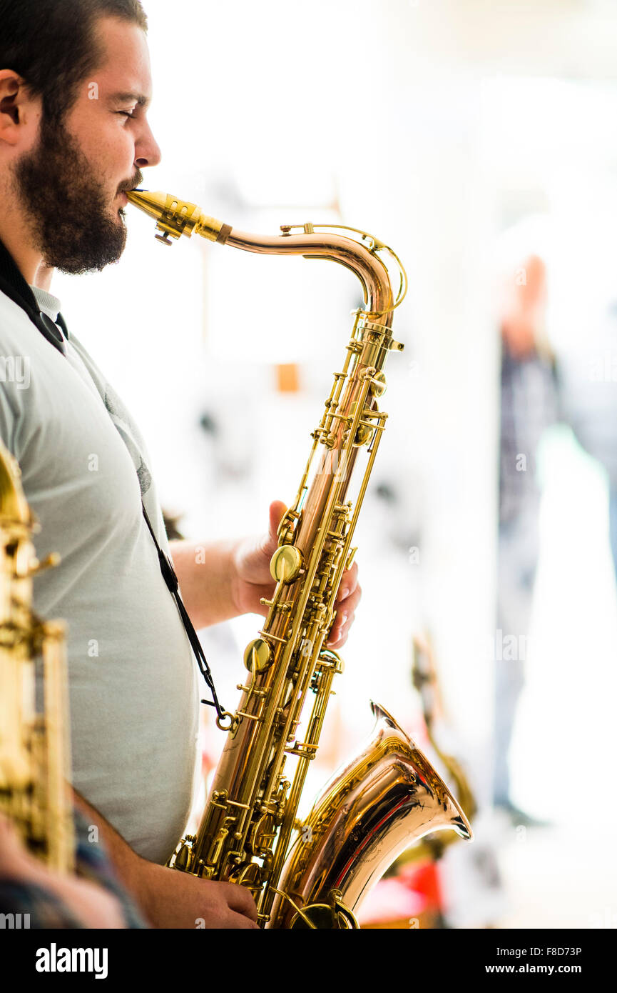 Jazz music : a musician playing a solo on his saxophone in a group - Stock Image