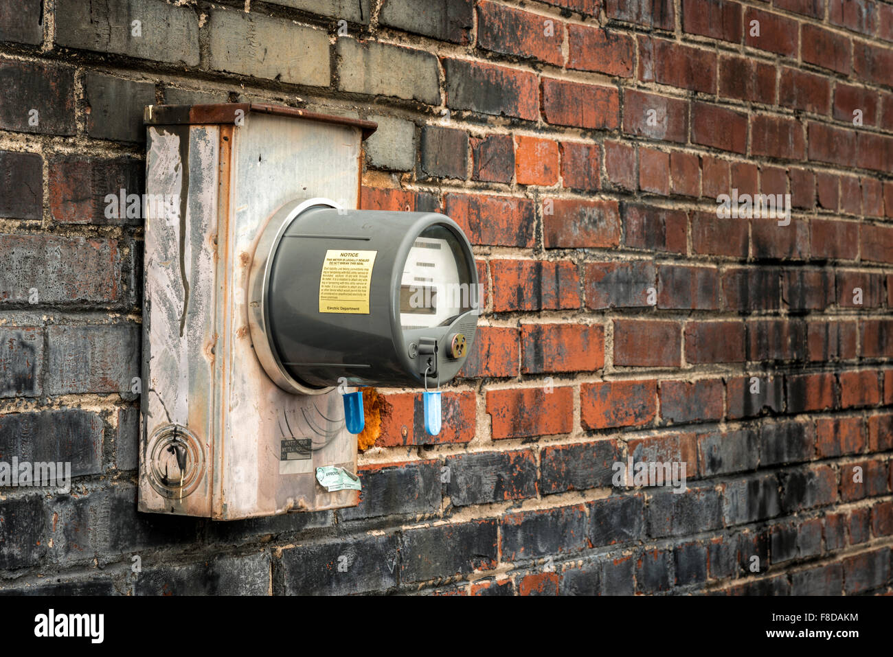 Electric Meter On Old Brick Wall of Commercial Building - Stock Image