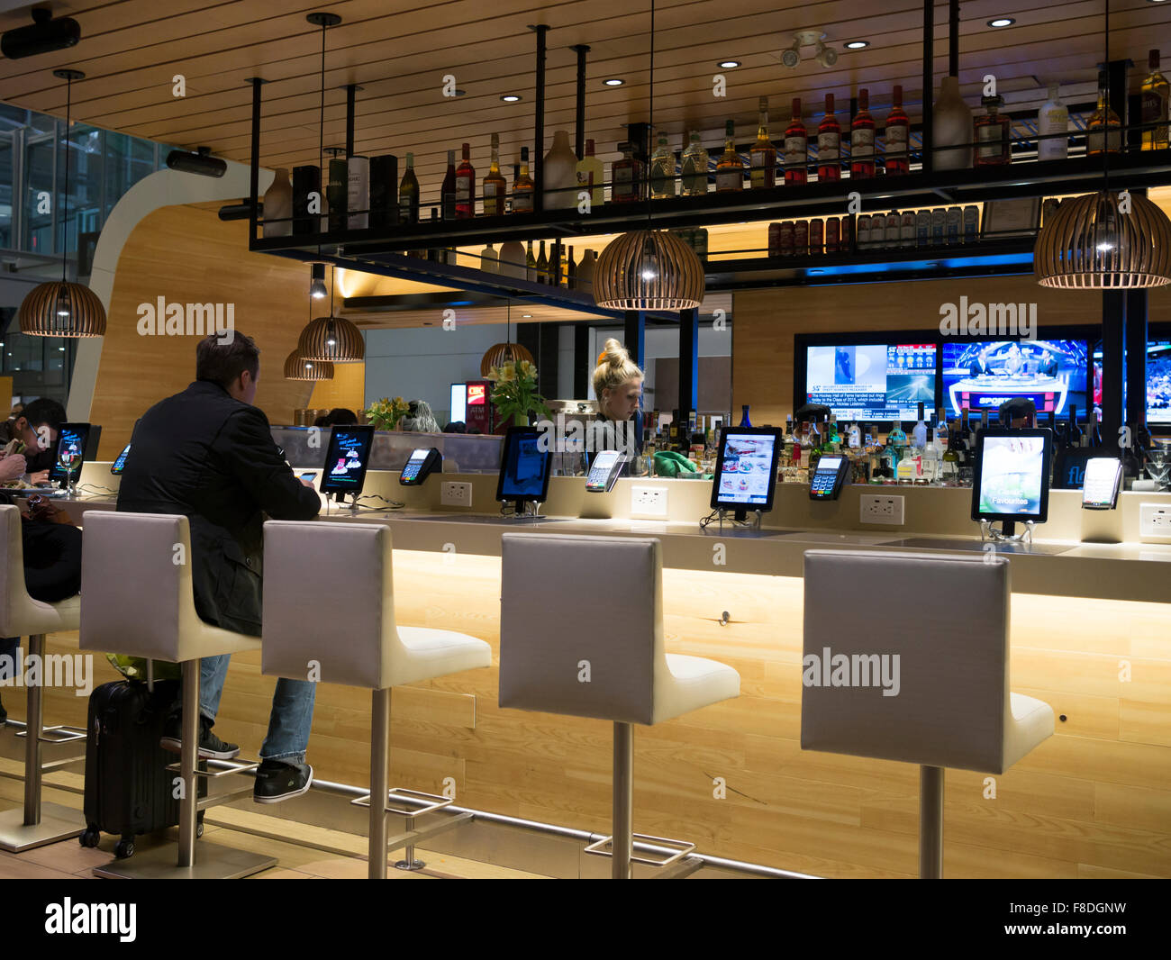 Toronto international airport Terminal 1 departure lounge bar. Tables connected with tablets and iPads for passenger - Stock Image