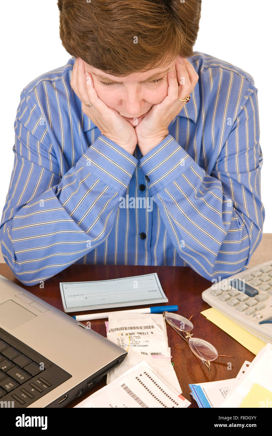 A middle aged woman holding her head in her hands having financial worries. - Stock Image