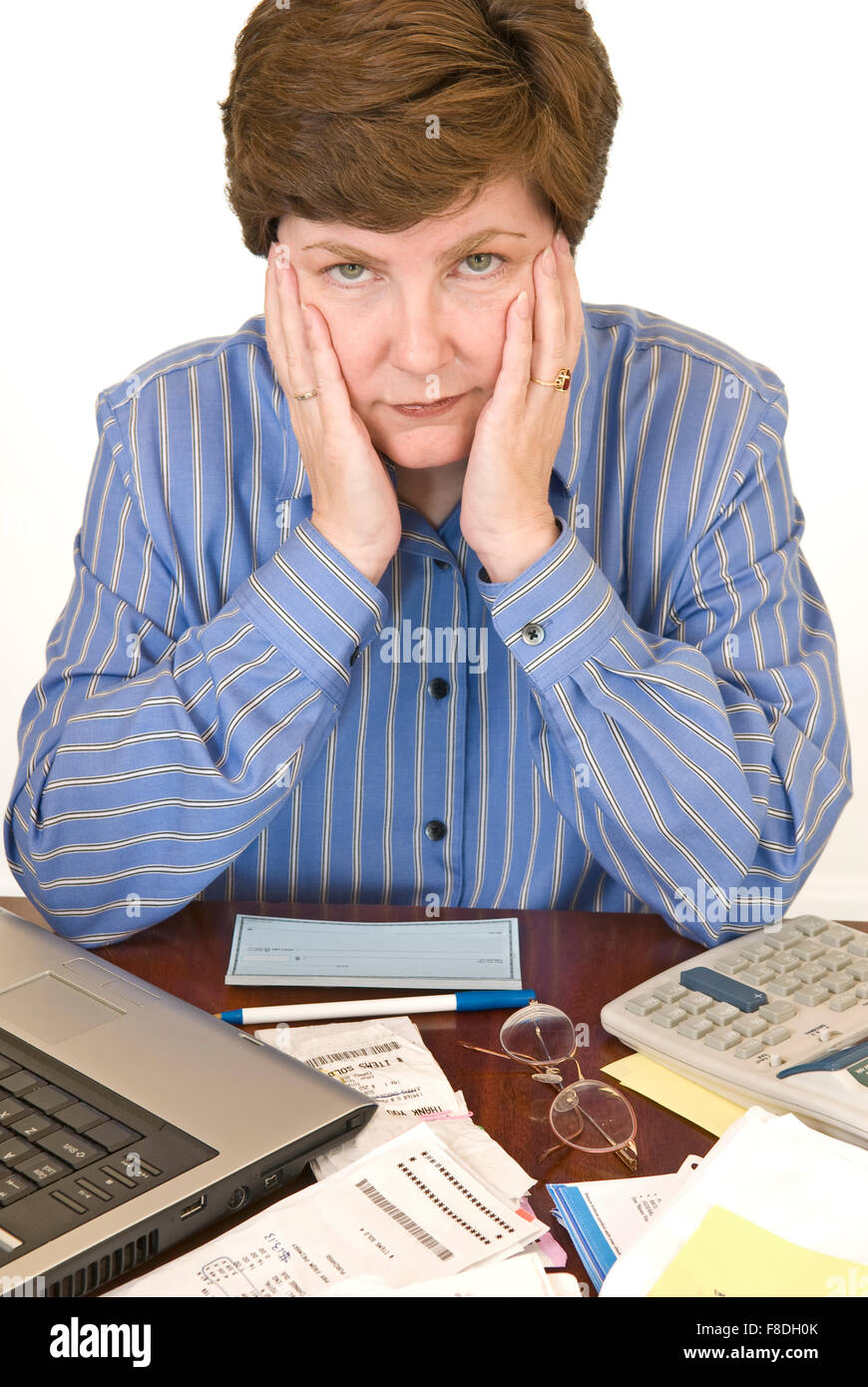 A Middle Aged Woman Surrounding by her Laptop, Checkbook, Calculator and Paperwork Looking Financially Overwhelmed. - Stock Image