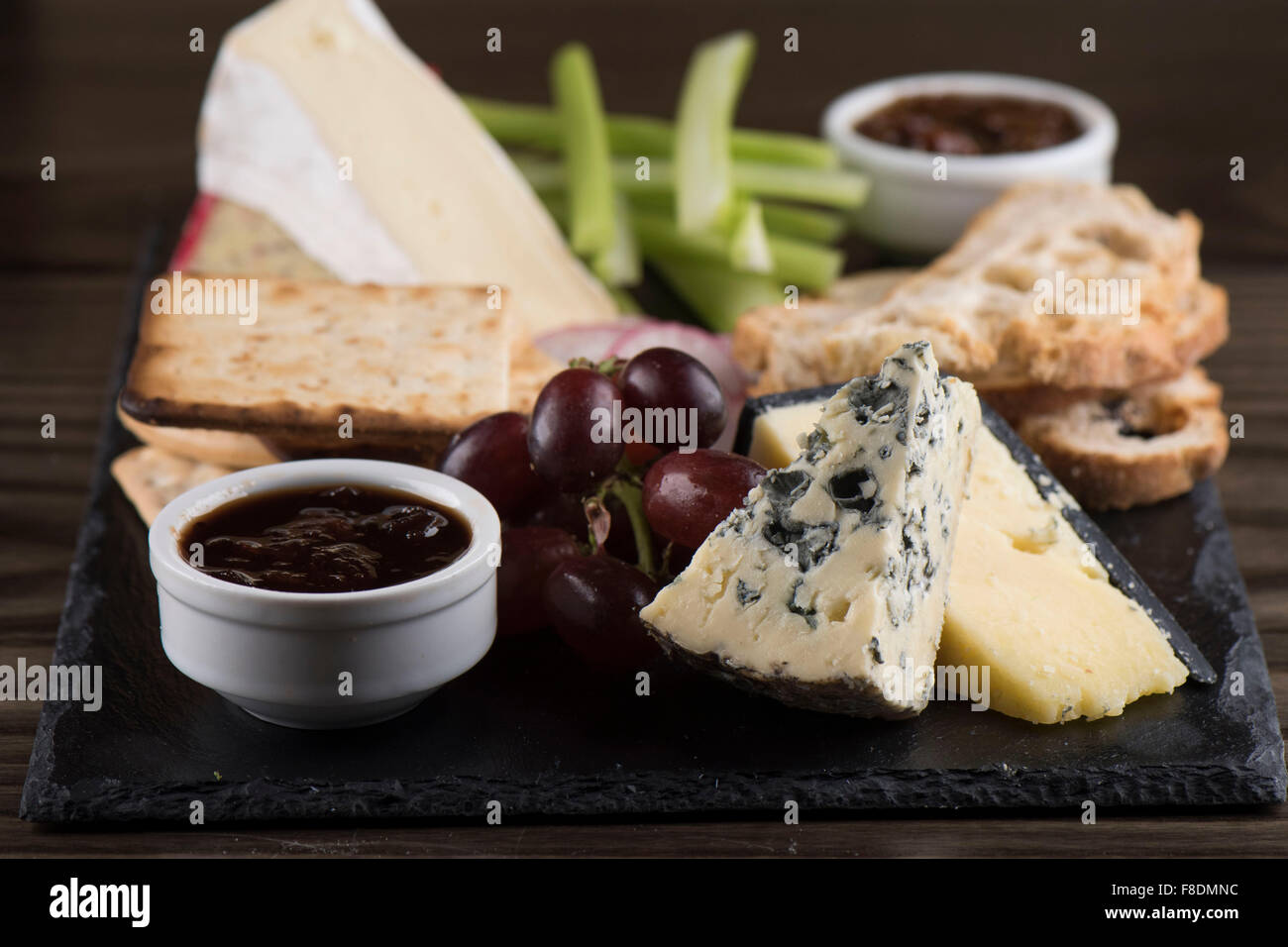 A cheese plate on slate with chutney, cheddar, stilton cheese, crackers, brie, grapes and celery. - Stock Image