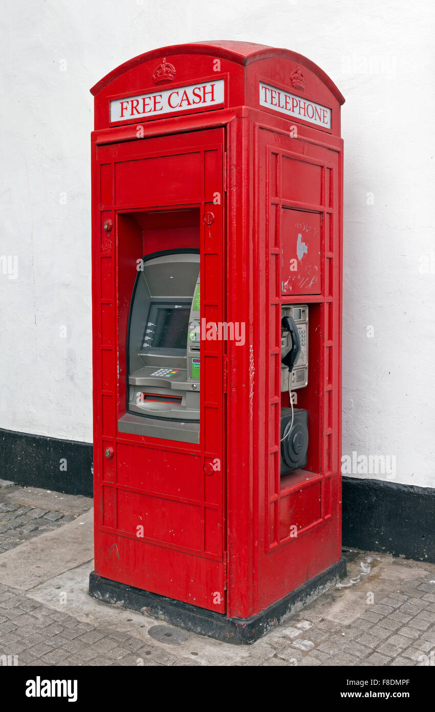 A traditional British red telephone box which has been modified to include a cash machine - Stock Image