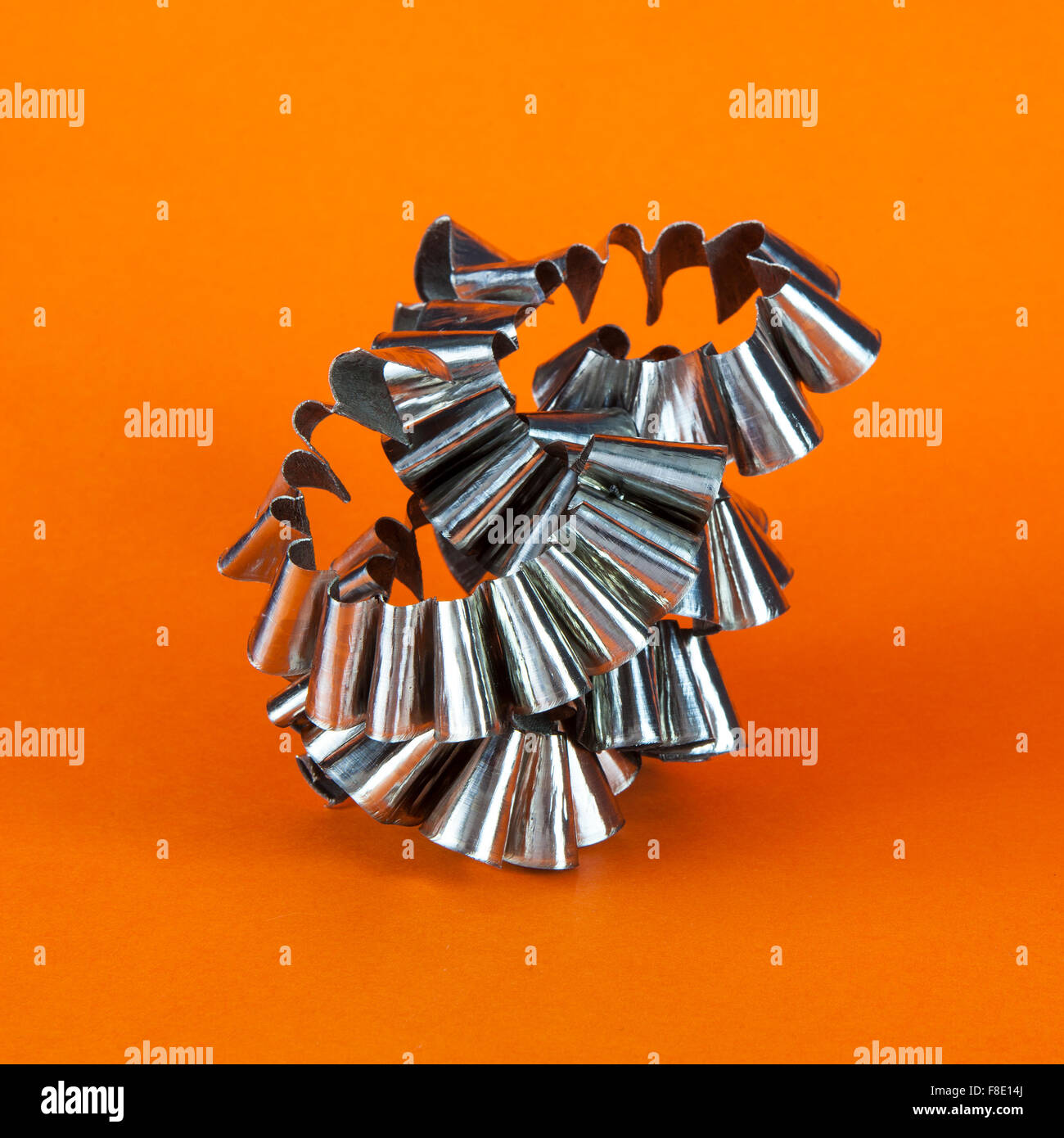 Metal Swarf on orange background - Stock Image