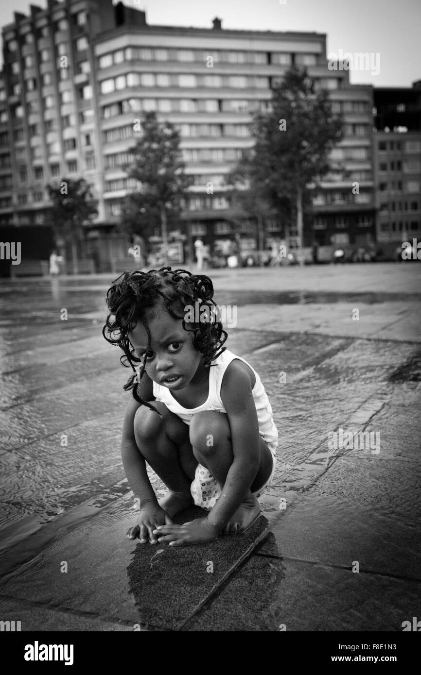 Black young girl on the Square of Flagey after the rain in a hot day in Brussels - Stock Image