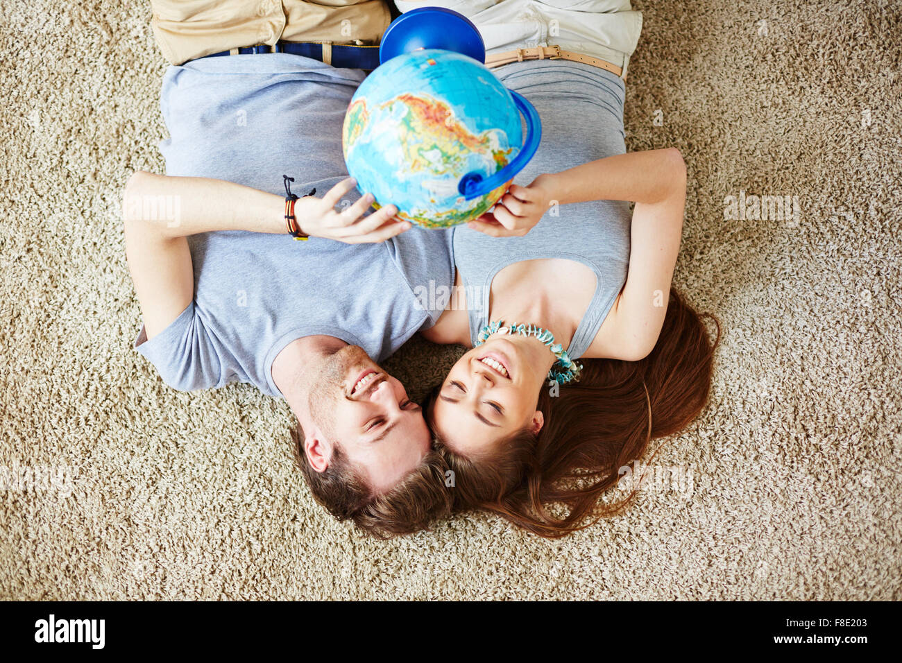 Restful couple with globe making plans for vacation - Stock Image