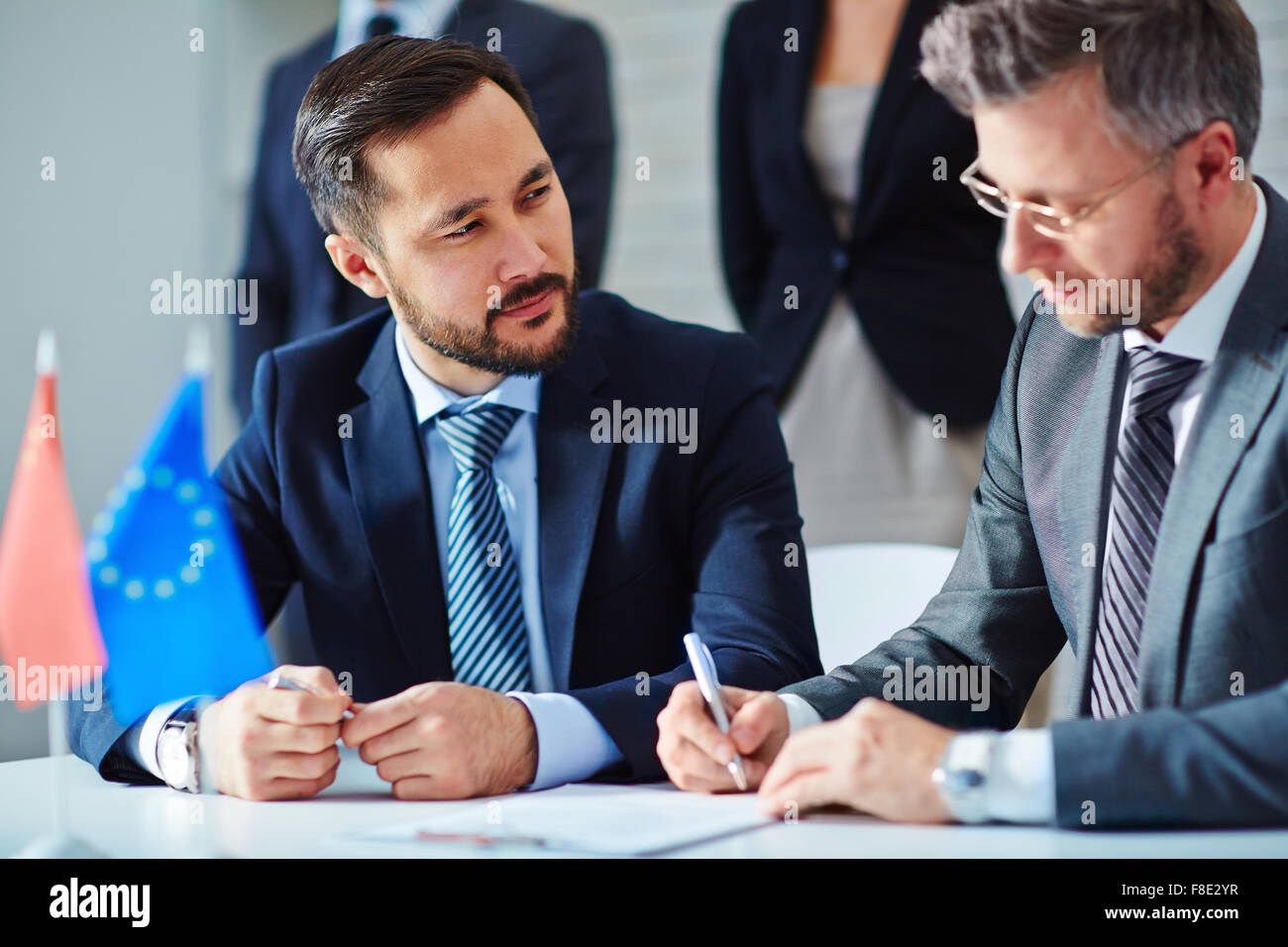 Two business leaders signing a contract at office - Stock Image