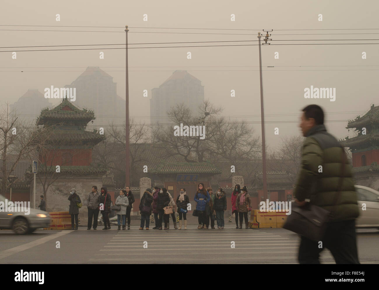 People with face masks wait at a pedestrian crossing on their way to work, braving heavy air pollution in the Chinese Stock Photo