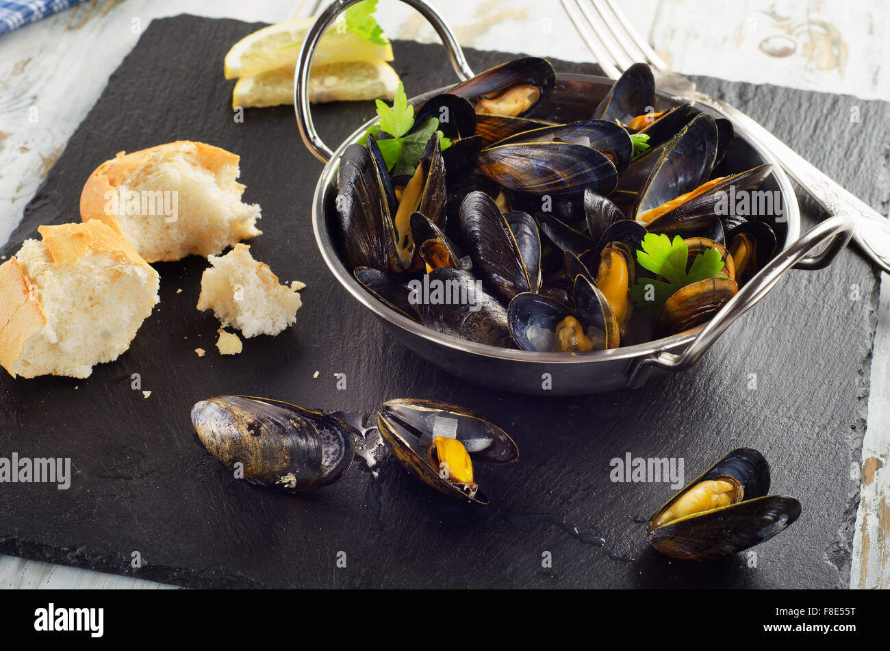 Boiled mussels in cooking dish on dark background. Selective focus Stock Photo