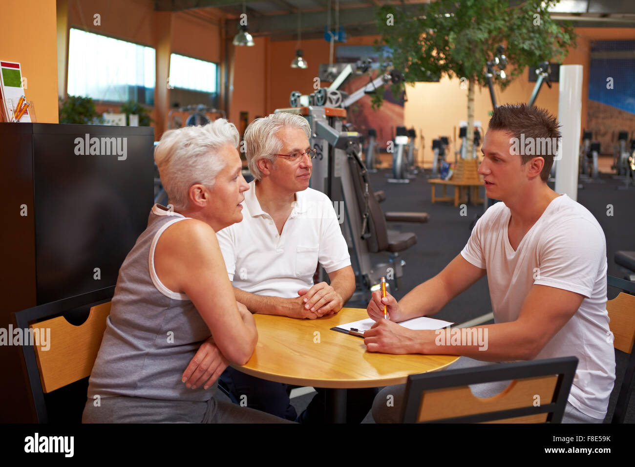 Fitness trainer in gym talking to new customers - Stock Image