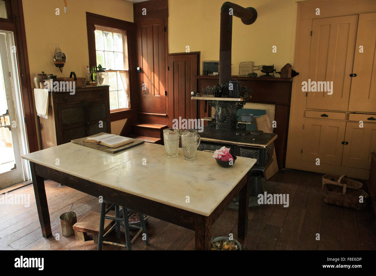 Kitchen area with cast iron stove in the background, old farmhouse. - Stock Image