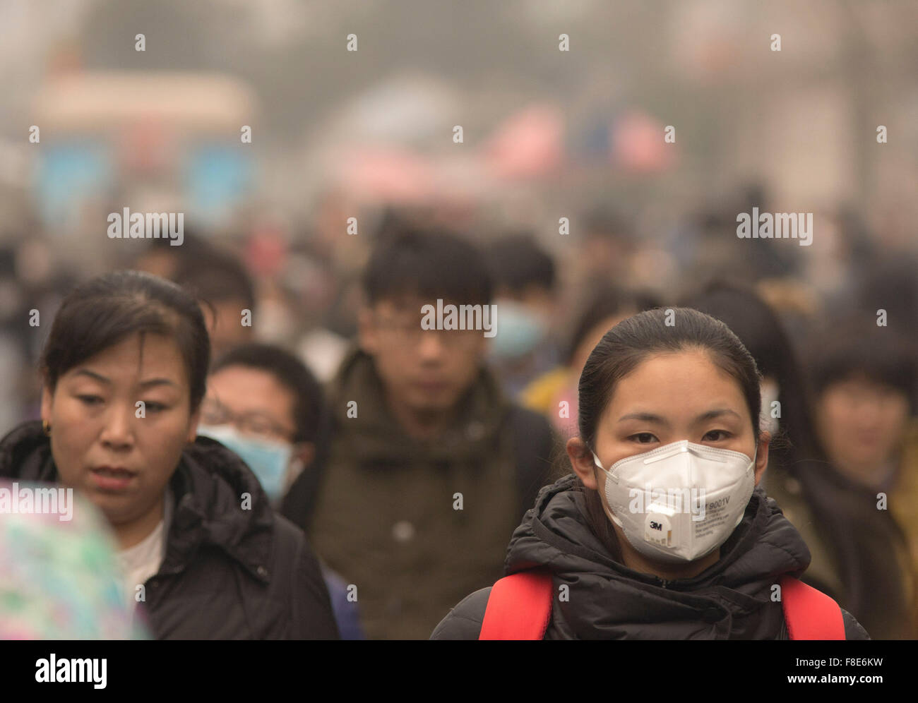 People and commuters wear face masks on their way to work, braving heavy air pollution in the Chinese capital city Stock Photo